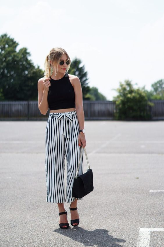 a black halter neckline crop top and black and white striped culottes, black heels