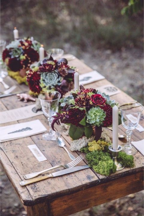 a wooden table with moss and bold burgundy and green centerpieces, candles and simple cutlery