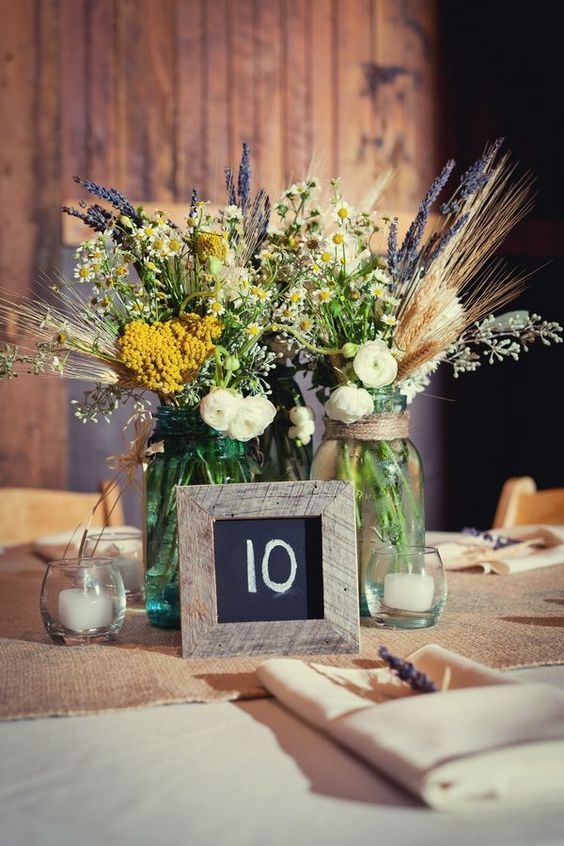 jars with wildflowers, candles and a framed table number for a cute rustic tablescape