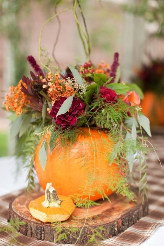 a pumpkin vase with a colorful floral and greenery arrangement as a fall wedding centerpiece