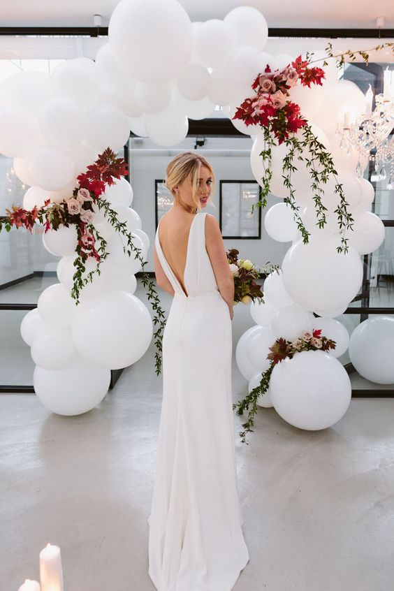 a wedding arch of oversized white balloons, foliage and dusty pink roses
