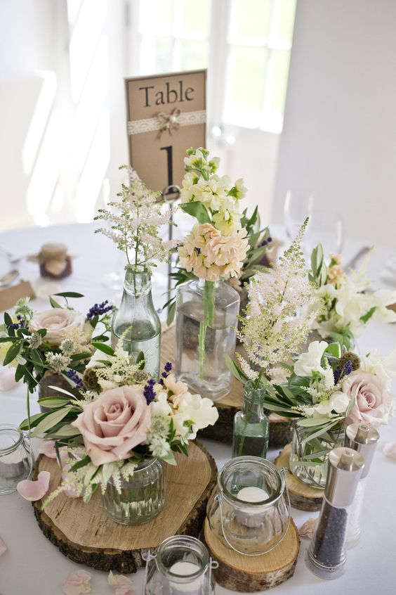a rustic centerpiece with wood slices, various flower arrangements, candles and a table number