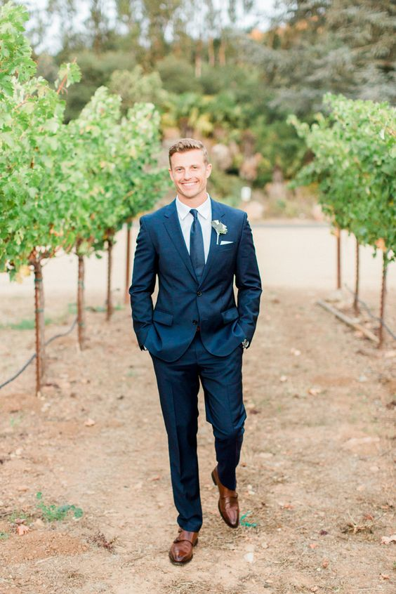 a navy two piece wedding suit with a matching tie and cognac shoes