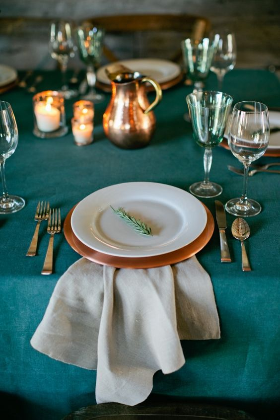 a teal tablecloth and glasses, copper chargers and jugs look chic