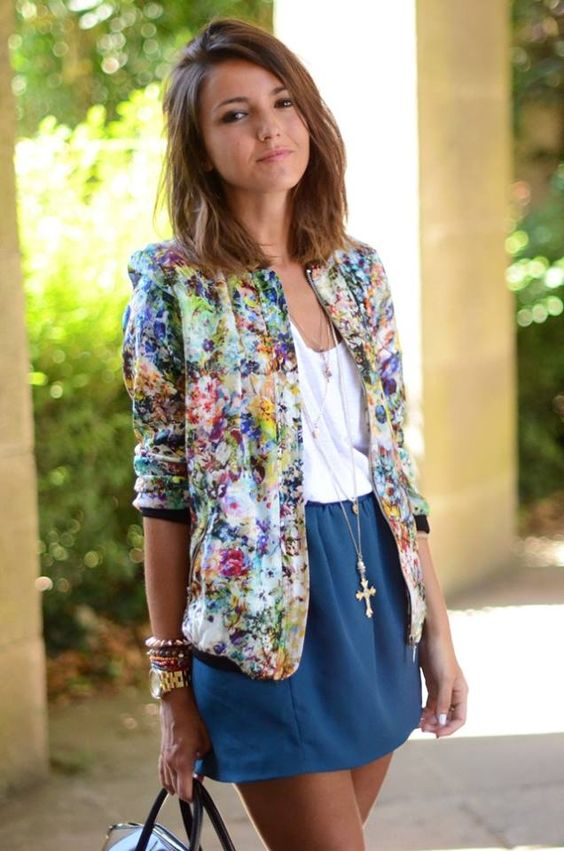 a blue mini skirt, a white top, a bold floral bomber and a tote