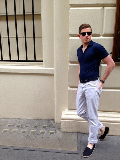 With navy blue shirt, white cuffed trousers and black belt