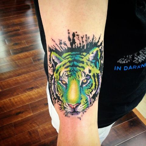 Green and yellow tiger tattoo on the hand
