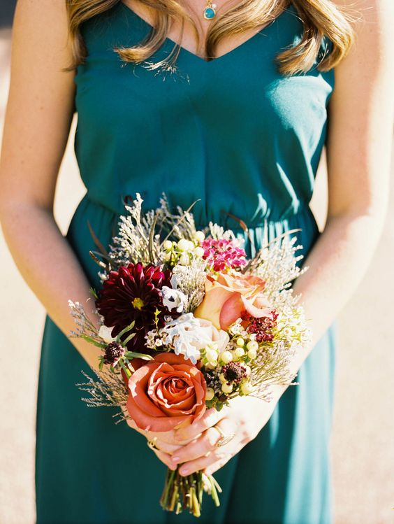 a teal bridesmaid's dress and necklace, a bouquet with copper blooms remind of the fall