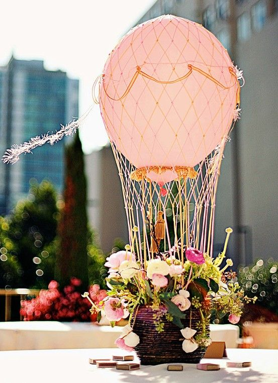 a hot air balloon wedding centerpiece with a basket of flowers and a pink balloon