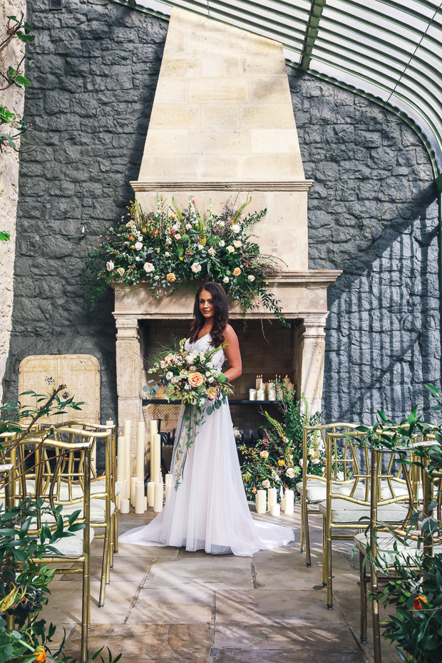 The lush florals in orange, cream and peach with lots of greenery and a cool warm-colored fireplace are an amazing space for the ceremony