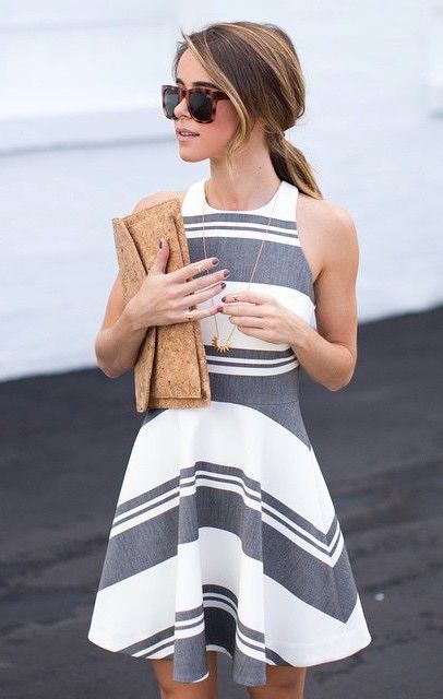 a grey and white striped halter neckline A-line dress and a neutral clutch