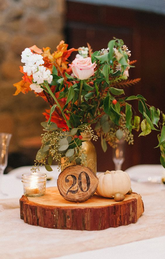 a wood slice with a wooden table number, a candle holder, a small pumpkin and a bold floral arrnagement will be a cool centerpiece