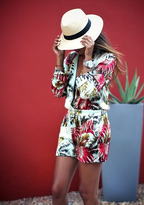 a tropical print romper with long sleeves and a plunging neckline and a straw hat
