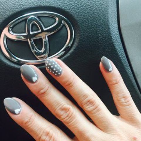 grey nails with polka dots and small hearts for accents