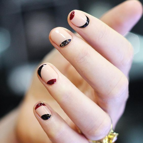 neutral round nails with black and red curves is a creative modern design