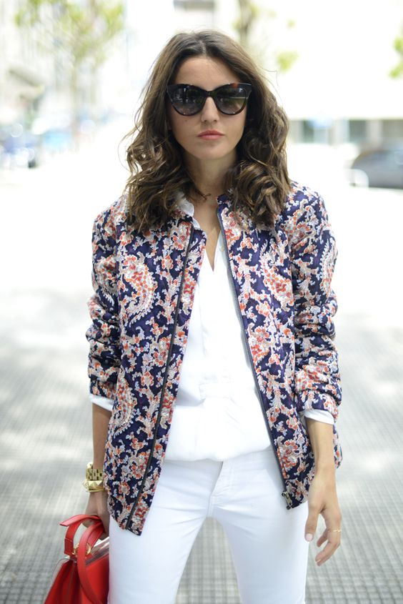 white pants, a white tee, a blue and red printed bomber jacket and a red bag