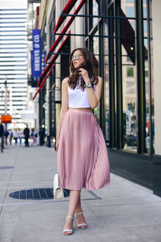a white halter neckline crop top and a pink pleated midi skirt, white heels and a bag