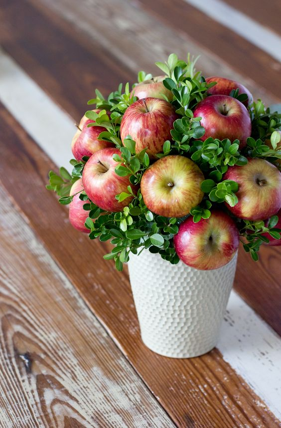 a white textural vase with boxwood and apples will be a nice and easy idea for a fall wedidng