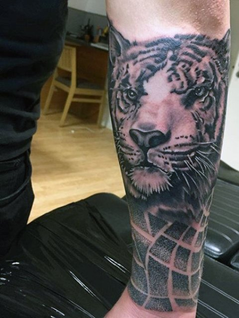 Tiger head tattoo on the forearm