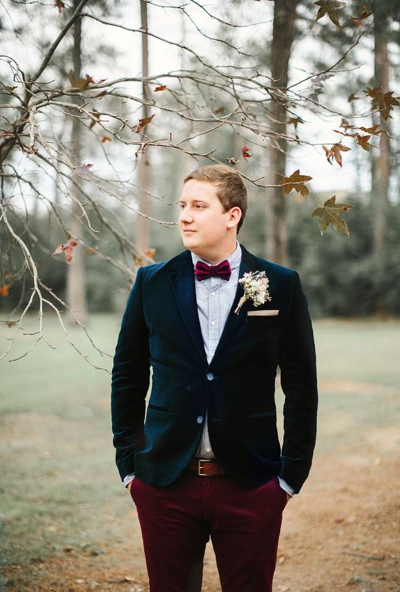 burgundy velvet pants, a navy velvet jacket, a light blue shirt and a burgundy bow tie