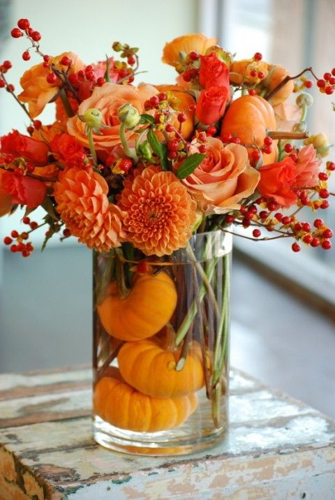 a bold floral arrangement in burnt orange and pumpkins in the vase for a fall wedding