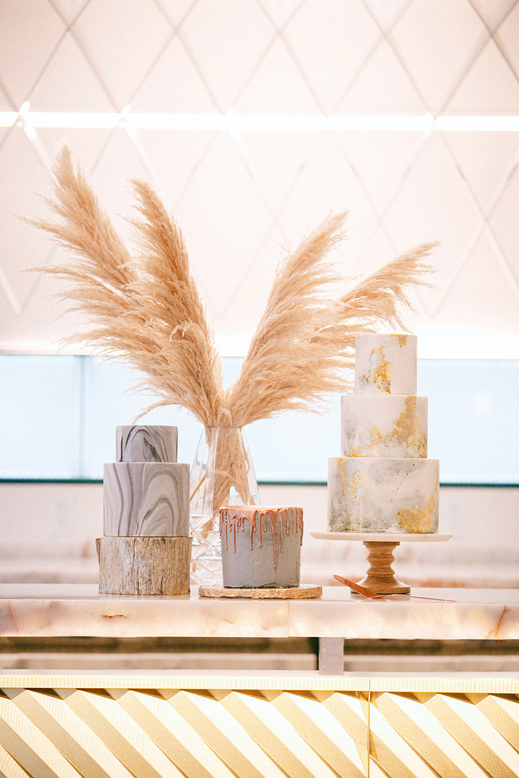 wedding cake tables - photo by Leigh Miller Photography http://ruffledblog.com/modern-wedding-inspiration-with-a-pampas-grass-chandelier