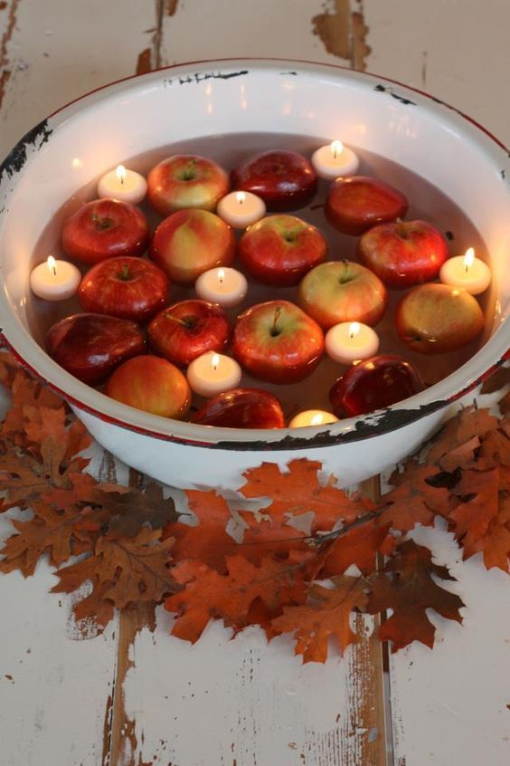 a metal bath with floating candles and apples surrounded with fall leaves is a chic idea for a rustic wedding