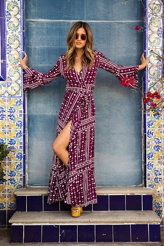 a burgundy and white printed wrap dress with long bell sleeves, a V neckline and a front slit