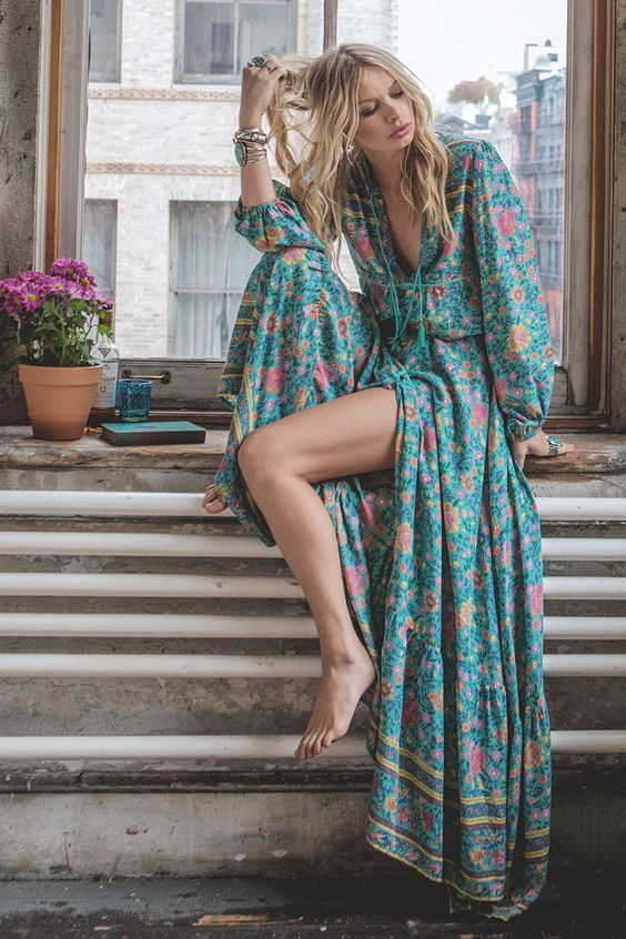 a colorful floral print maxi dress with long sleeves, a deep laced up V cut and a front slit