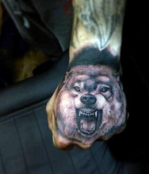Realistic wolf tattoo on the hand