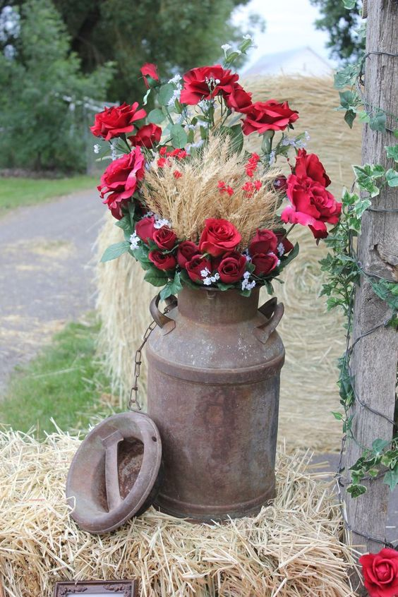 an old milk churn with red roses, greenery and wheat is awesome for any rustic celebration