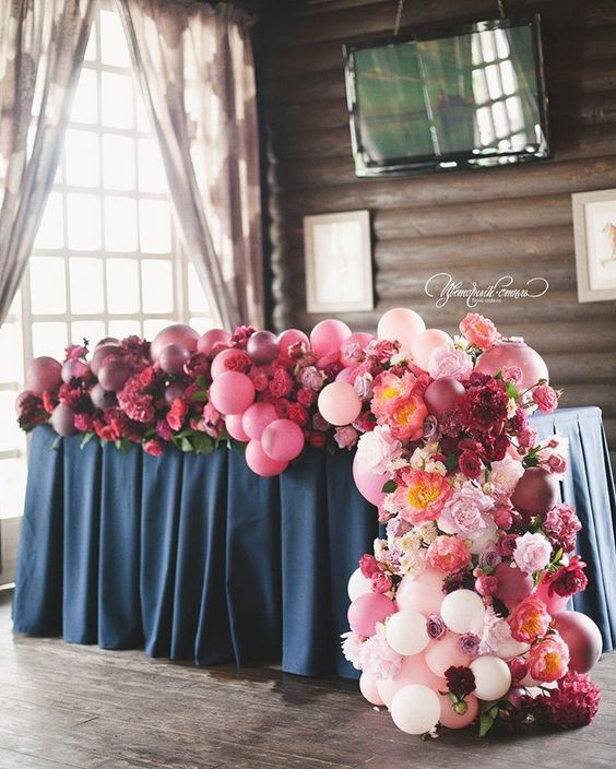 a sweetheart table decorated with an ombre pink to plum balloon and bloom garland