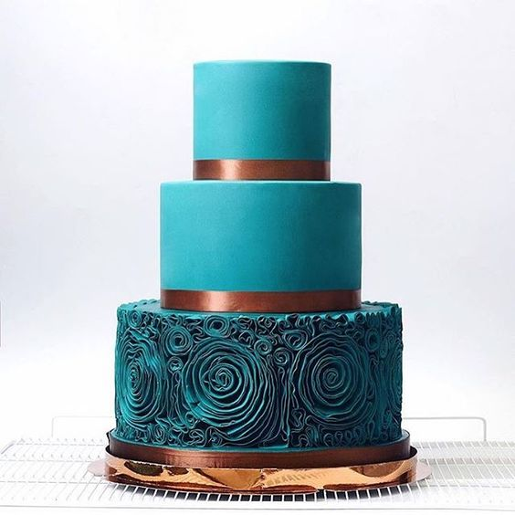 a teal wedding cake with a ruffle rose layer and copper ribbons