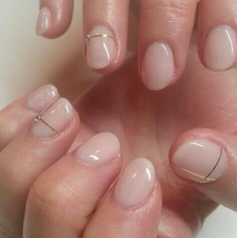 blush round nails with gold stripes and rhinestones
