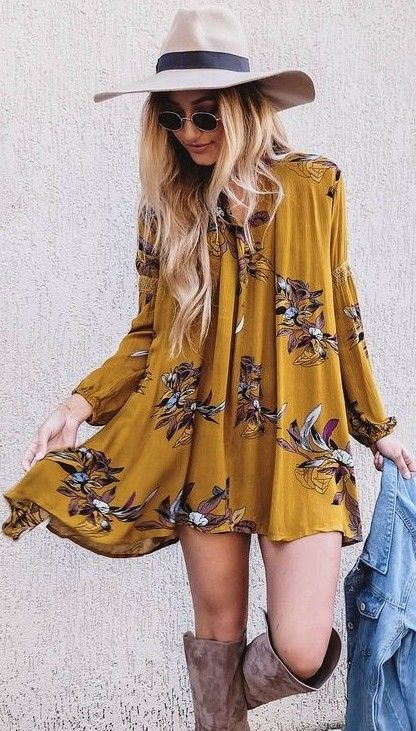 a mustard mini dress with long sleeves and a floral print with suede boots and a hat