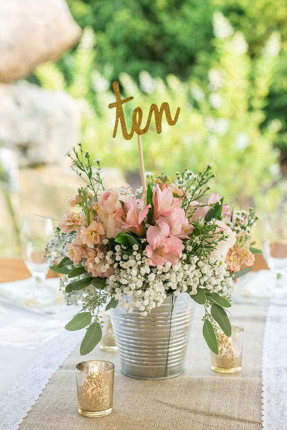 a bucket with a pink floral arrangement and a glitter table number