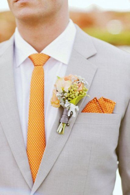 a light grey suit with a white shirt and a polka dot orange tie and a handkerchief
