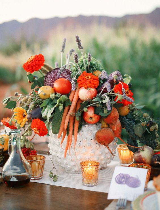 a fall centerpiece with red flowers, apples, carrots, beets, leaves and lavender