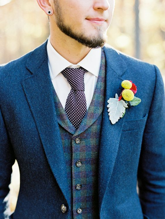 a bold blue suit, a checked vest and a knit printed tie