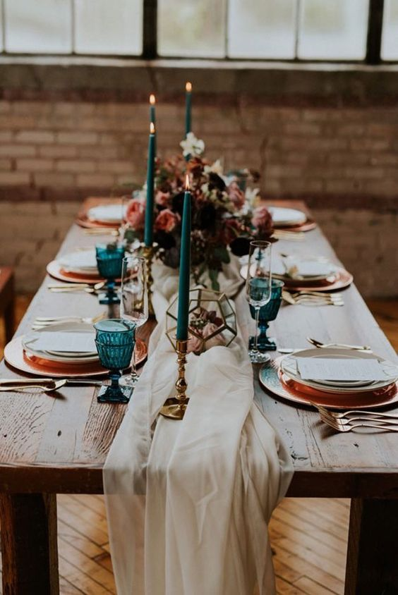 teal cnadles and glasses and copper chargers and flatware look very chic and embrace the fall