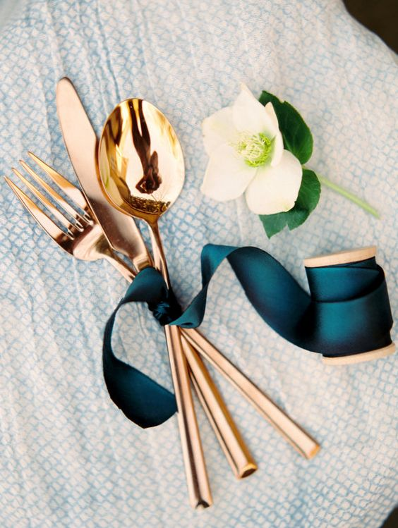 copper flatware tied with a teal ribbon for an elegant table setting