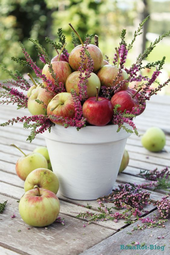 a white planter filled with apples and wildflowers for a summer or spring wedding