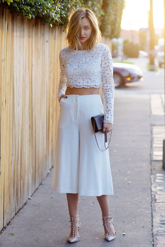 a lace long sleeve crop top and culotte pans, spike shoes and a black clutch
