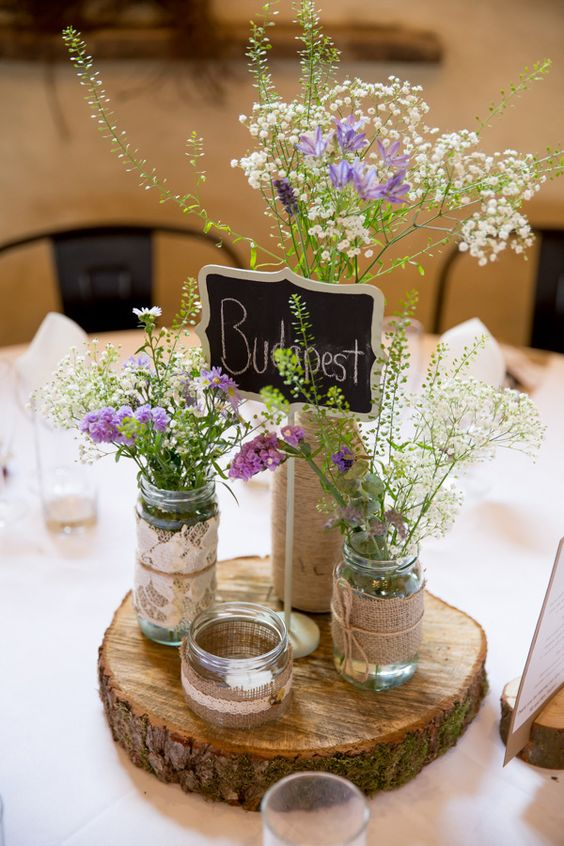 a wood slice with jars covered with burlap, jute and lace, wildflowers and a chalkboard table name