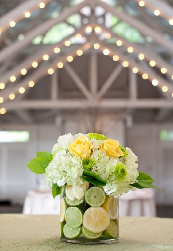 a glass vase with lime and lemon slices, red roses and white hydrangeas is great for a tropical wedding