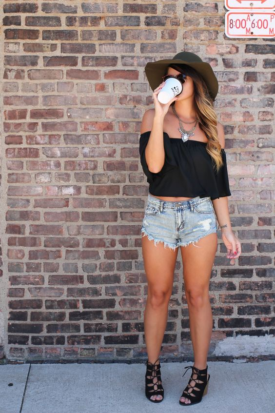a black off the shoulder crop top, distressed denim shorts and black suede lace up shoes