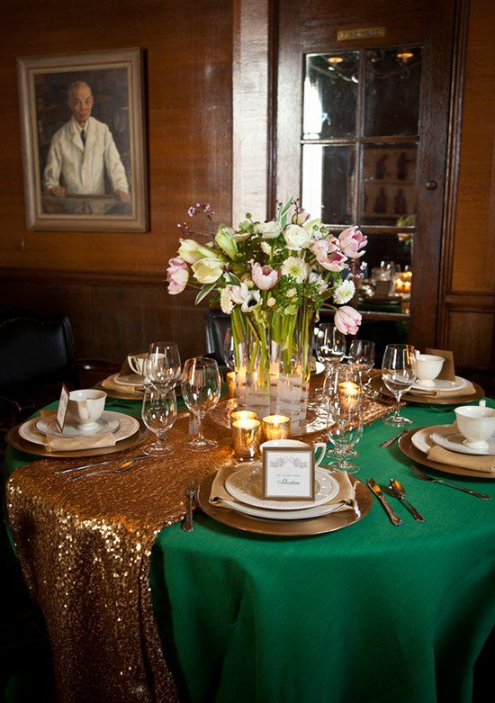 a gold table runner over an emerald tablecloth for a glam fall wedding