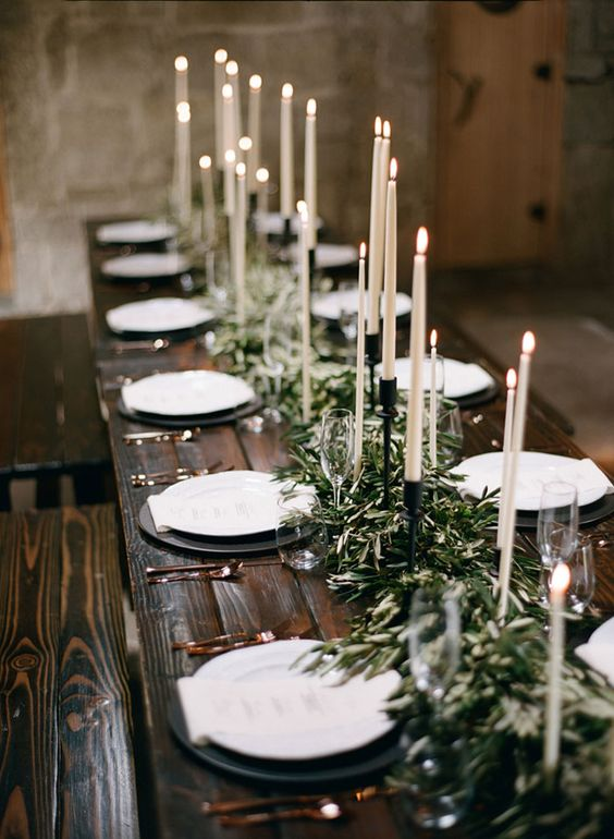 a dark stained wooden table with an olive branch table runner and candles