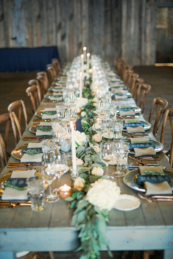 a tablescape with a lush greenery and peachy bloom runner, candles and copper flatware
