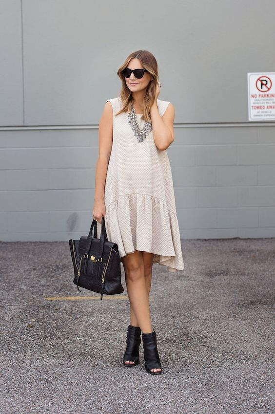 a neutral drop waist dress without sleeves, black leather peep toe booties and a matching tote